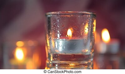 Burning decorative candle in glass candlestick on a blurred...