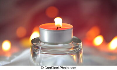 Burning decorative candle on glass candlestick on a blurred background