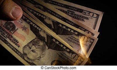 Burning dollars close up over black background Slow motion