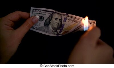 Burning dollars in a hand close-up on a black background -...