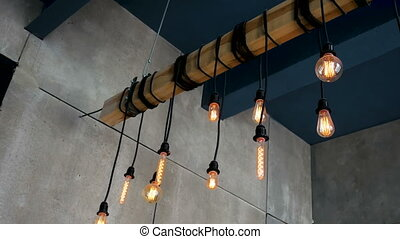 burning Edison bulbs different shape hanging on a beam in...
