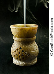 Burning frankincense in a stone censer over black...