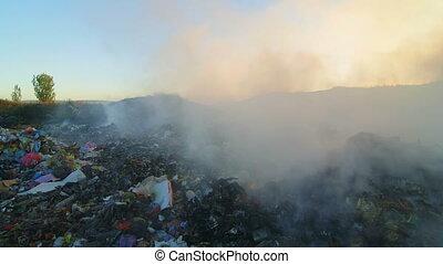 Burning garbage toxic smoke rises into the air pan shot