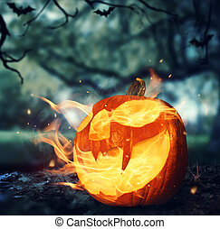Burning halloween pumpkin in a forest at night