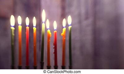 Burning hanukkah candles in a menorah on colorful candles...
