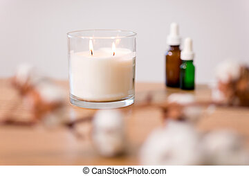 burning home fragrance candle in glass holder