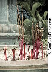 Burning incense in urn at buddhist pagoda