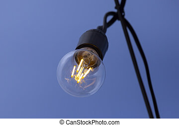 burning lamp on the background of blue sky