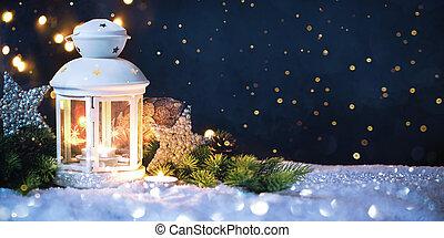 Burning lantern in the snow at night