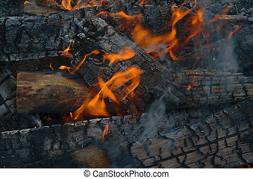 Burning log of wood close-up as abstract background. The hot embers of burning wood log fire.