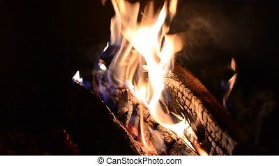 Burning logs and blazing flames in fireplace.