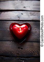 Burning love - Image of red heart shaped candle burning on...