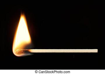 Horizontal burning match isolated on black background.