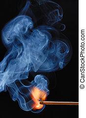 Burning Match - Macro of burning match and smoke on black...
