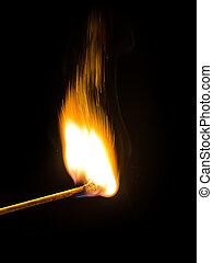 Burning match over black background
