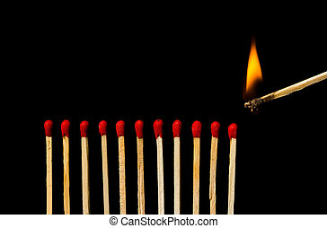 Burning match with row of matches isolated on black background