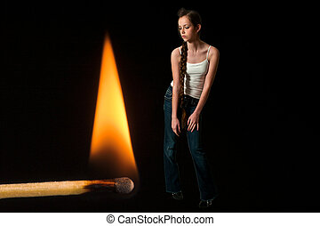 Woman standing next to a burning match