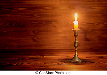 burning old candle with vintage brass candlestick on wooden...