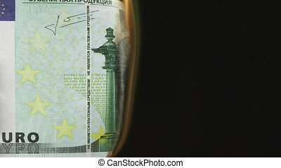 Burning one hundred Euro banknote on a black background...