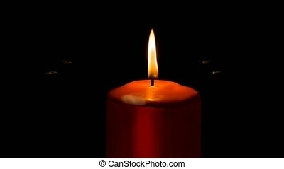 Burning red candle isolated on black background and animated...