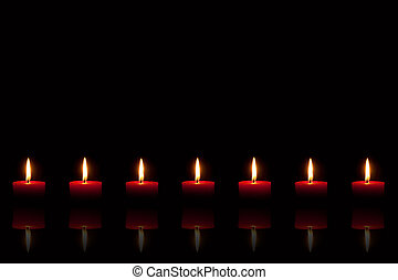 Row of seven burning red candles in front of black background, with reflection