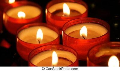Burning red round candles in catholic church - Burning red...
