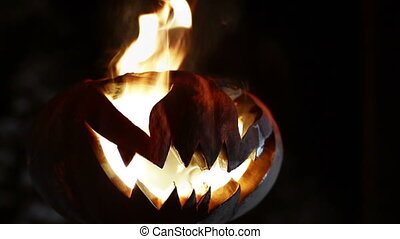 Burning smile pumpkin on Halloween. Looped - Glowing in the...