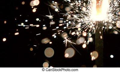 Burning sparkler against black background. Super slow motion shallow focus video