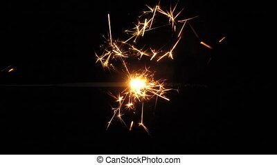 Burning sparkler on black background