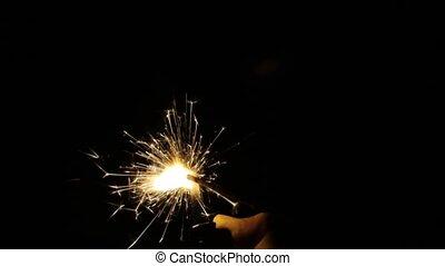 burning sparkler or bengal light in darkness - holidays, new...