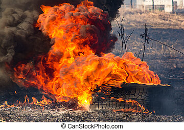 Burning tire on a grass field in the spring