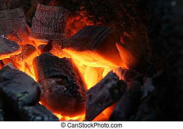 burning wood coals - A craftsman/blacksmith working metal...