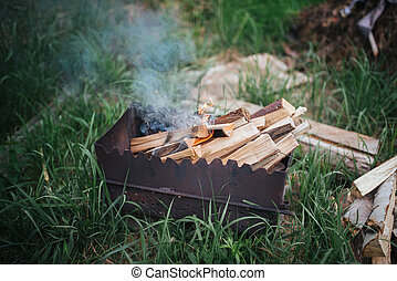 Burning wood in a brazier on the background of grass
