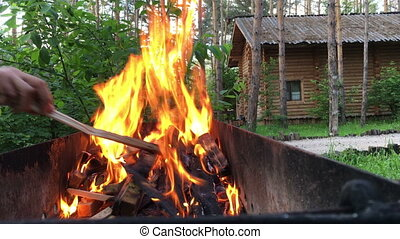 Burning wood in a brazier. Strong fire in the grill.
