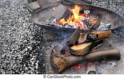 Burning wood of campfire in metal fire bowl on a pebble floor