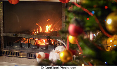 Burning wooden logs in fireplace decorated for Christmas
