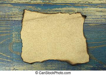 burnt paper on blue old wood background