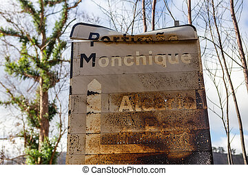 Burnt sign on the road after a forest fire in Monchique, Portugal. Portimao, Monchique, Alcaria do Peso, village name, weight.