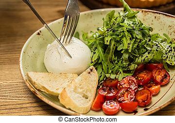Burrata mozzarella cheese, tomato and bread, selective focus