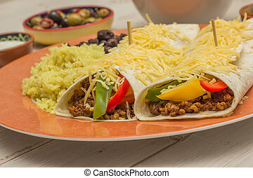 Burritos filled with ground beef and peppers with rice and black beans on the side