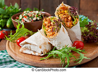 Burritos wraps with minced beef and vegetables on a wooden ...