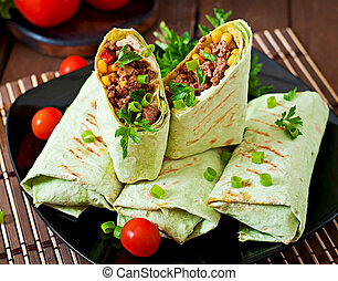 Burritos wraps with minced beef and vegetables on a wooden...