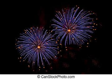 Bursts of Blue and Orange Fireworks against a black sky