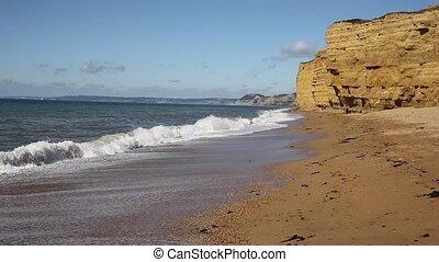Burton Bradstock sandstone cliffs and waves crashing in to...