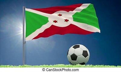 Flag of Burundi fluttering and soccer ball rolls on lawn, 3d rendering