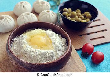 Buryat cuisine. Egg in flour, bouzou, greens, tomatoes on a...