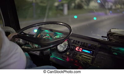 Bus driver at the wheel riding intercity coach on night road in the city