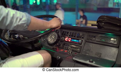 Bus driver sits behind the steering wheel of intercity coach at night station