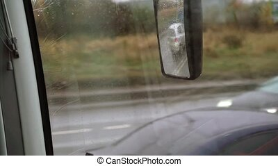 Bus driving at rainy day mirror