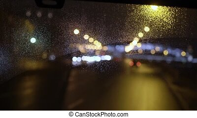 Bus driving at rainy night window